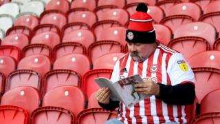 A Brentford fan reads a programme