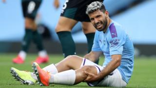 Manchester City striker Sergio Aguero appears in pain as he sits up after injuring his knee against Burnley in June