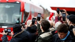 Liverpool fans take pictures of the team bus arriving