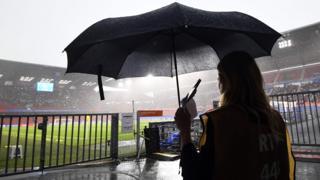 Journalist holds an umbrella