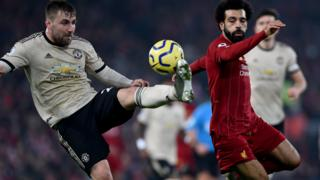 Manchester United's Luke Shaw and Liverpool Mohamed Salah battle for possession