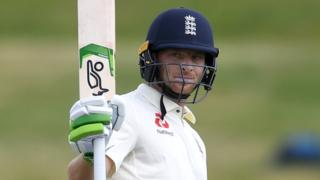 England batsman Jos Buttler raises his bat to celebrate making a century against New Zealand A