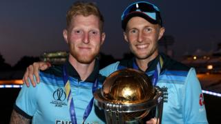 England players Ben Stokes (left) and Joe Root (right) smile as they hold up the men's World Cup trophy