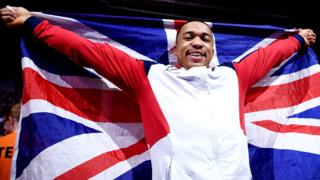 British gymnast Joe Fraser holds up the Union Jack after winning World Championship gold in the men's parallel bars