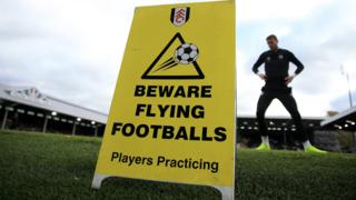 A beware of flying footballs sign at Craven Cottage