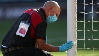 A Southampton member of staff cleans the goalpost