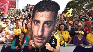 Fans hold a cutout of Daniel Ricciardo's face