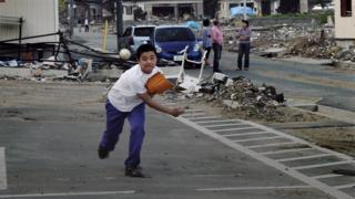 A young Japanese boy pitches a baseball in the aftermath of the Fukushima disaster