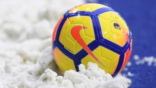 A Premier League ball surrounded by snow during the winter