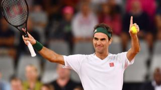 Roger Federer raises his hands in celebration