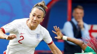Lucy Bronze with Phil Neville in the background