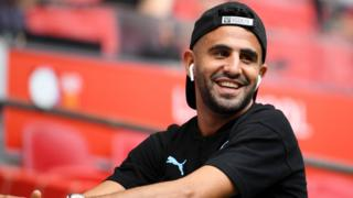 A picture of Riyad Mahrez at Wembley, smiling, with headphones in and wearing a cap backwards