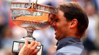 Nadal brings the trophy to his forehead
