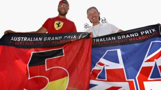 F1 fans hold up Vettel and Hamilton flags