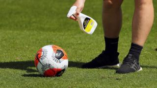 A man disinfects a Premier League football at training session