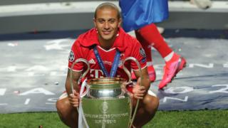 Thiago crouches down with the Champions League trophy