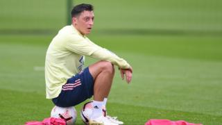 Mesut Ozil sits on a football during an Arsenal training session