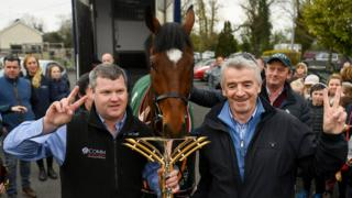 Trainer Gordon Elliott (left) and owner Michael O'Leary (right) hold up two fingers beside Tiger Roll to signify the horse's two successive Grand National wins at a homecoming parade in Summerhill