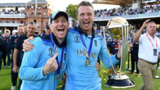 England captain Eoin Morgan (left) and vice-captain Jos Buttler (right) smile as Buttler holds up the World Cup trophy