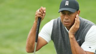 Tiger Woods lines up a putt