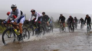 Cyclists ride through a big puddle