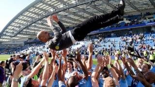 Pep Guardiola is thrown into the air by his Manchester City players