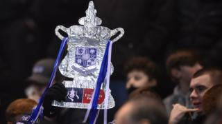 A fan holds up a tin foil FA Cup