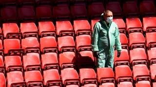 A Liverpool staff member at Anfield in full PPE