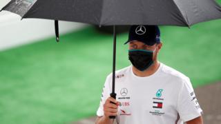 Valtteri Bottas carries an umbrella