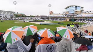 India fans shelter from the rain