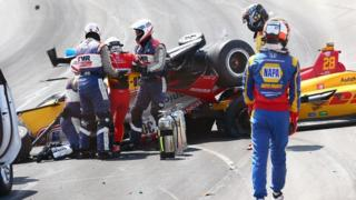Takuma Sato is removed from his car at Pocono