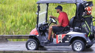 Tiger Woods driving a golf cart