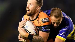 Jordan Rankin of Castleford Tigers is tackled by Jason Clark of Warrington Wolves