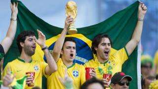 Brazil fans lift a World Cup in 2014 during Brazil v Chile