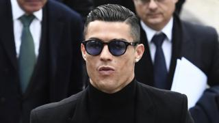 Ronaldo in close-up, wearing black clothes, with slick combed-back hair and sunglasses, flanked by men in suits