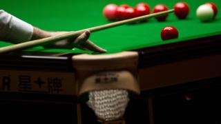 Snooker player prepares for a shot