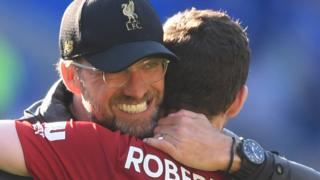 Liverpool manager Jurgen Klopp embraces defender Andy Robertson