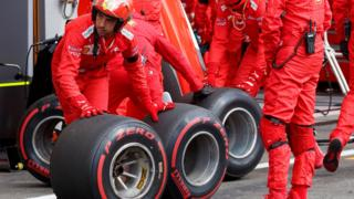 A Ferrari mechanic moves tyres