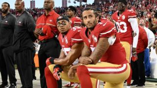San Francisco 49ers players Eric Reid (left) and Colin Kaepernick (right) kneel during the US national anthem before an NFL game