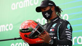 Lewis Hamilton holds Michael Schumacher's race helmet