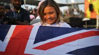 Sky Brown smiling as she holds a union flag