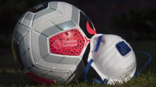 A Premier League branded match ball rests on grass next to a face mask