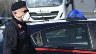 An Italian Carabinieri wearing a respiratory mask stands at a police check-point few kilometers from the small town of Castiglione d'Adda, southeast of Milan