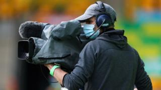 A camera operator wears a face mask as he films at a football match in Norwich