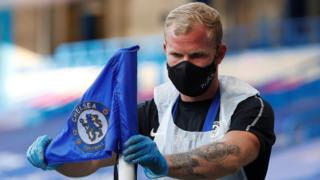 A Chelsea member of staff adjusts the corner flag