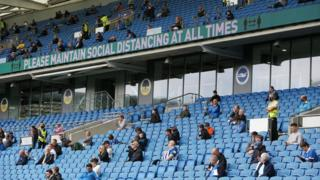 Socially-distanced fans watch a friendly between Brighton and Chelsea at the Amex Stadium