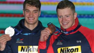 Adam Peaty and James Wilby pose with their gold and silver medals from the World Championships