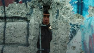 An East German guard peers through a whole in the Berlin Wall