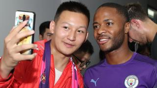 Raheem Sterling poses for a selfie with a fan in China