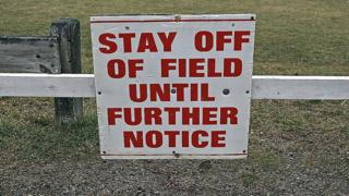 Stay off the field sign